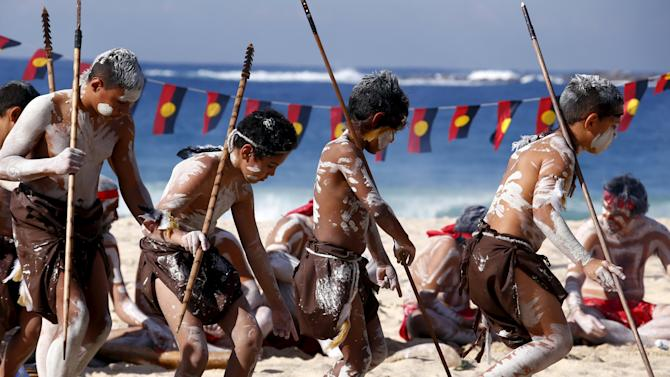 Traditonally dressed Australian Aboriginal performers hold spears as they participate in a 'Corroboree' showcasing traditional dance during an event to mark National Reconciliation Week on Sydney's Coogee Beach