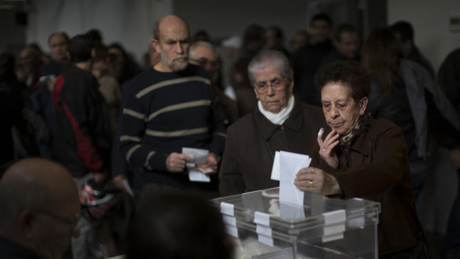 A woman casts her vote in a polling station in Barcelona, Spain, on Sunday, Nov. 25, 2012. Voters in Catalonia begin casting their ballots in regional elections that could determine the future shape of Spain. If voters give the regional government strong support, its leader pledged to hold a referendum asking Catalans if they'd prefer to split from Spain and go it alone in the 27-member EU. (AP Photo/Emilio Morenatti)