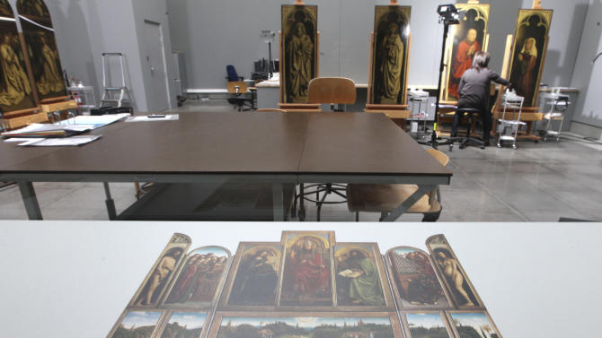 FILE - In this Oct. 11, 2012 file photo, a restorer inspects, also visible in the foreground, one of the 24 framed panels of the Altarpiece or Adoration of the Mystic Lamb, at the Fine Arts museum in Ghent, Belgium. If Rotterdam's stunning heist of Picasso, Monet and Matisse paintings last month focused attention on the murky world of art theft, Ghent's gothic Saint Bavo cathedral has been at the center of a crime that has bedeviled the art world for decades. The Just Judges panel of the Van Eyck brothers' multi-panel Gothic masterpiece hasn't been seen since 1934, when chief suspect Arsene Goedertier suffered a stroke at a political rally close to Ghent and died after murmuring possibe clues to the crime to a  confidant. (AP Photo/Yves Logghe, File)
