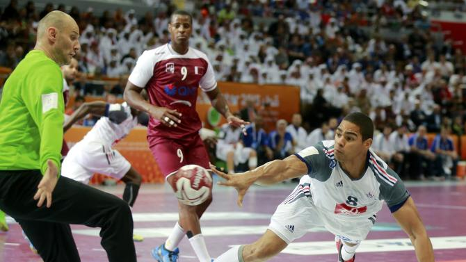 Narcisse of France shoots past goalkeeper Saric of Qatar during their final match of the 24th Men's Handball World Championship in Doha