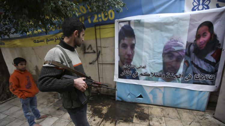 A Lebanese anti-Syrian regime gunman looks at a poster shows a portrait of Malek Haj Deeb, 20, left, with his two friends who were three of several of the young Lebanese men who were killed in neighboring Syria's civil war last week, in the poor neighborhood of Mankoubeen, in the northern port city of Tripoli, Lebanon, Wednesday Dec. 5, 2012. The families of several of the young Lebanese men who were killed in Syria last week say their sons were more interested in fashion and swimming holidays than fighting in a foreign war. But when the men's corpses turned up in Syria, the government in Damascus said they were part of the stream of foreign jihadists pouring into the country to fight alongside rebels. (AP Photo/Hussein Malla)