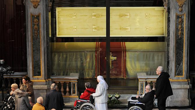 "Faithful pass by the Shroud of Turin that went on display for a special TV appearance Saturday, March 30, 2013. The Shroud went on display amid new research disputing claims it's a medieval fake and purporting to date the linen some say was Jesus' burial cloth to around the time of his death. Pope Francis sent a special video message to the event in Turin's cathedral, but made no claim that the image on the shroud of a man with wounds similar to those suffered by Christ was really that of Jesus. He called the cloth an ""icon,"" not a relic — an important distinction. ""This image, impressed upon the cloth, speaks to our heart and moves us to climb the hill of Calvary, to look upon the wood of the Cross, and to immerse ourselves in the eloquent silence of love,"" he said. (AP Photo/Alessandro Di Marco, Pool)"