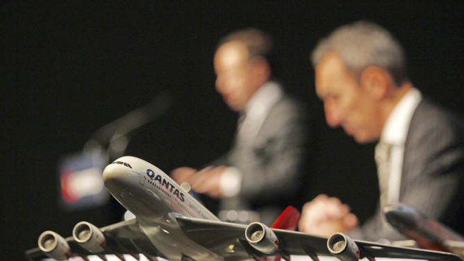 A model plane sits on a table as Qantas CEO Alan Joyce, left, discusses the airline's full-year financial results as CFO Gareth Evans listens in Sydney, Thursday, Aug. 23, 2012. Qantas Airways Ltd. reported a 245 million Australian dollar ($257 million) annual loss in profits on Thursday, hurt by rising fuel prices, a series of strikes that temporarily grounded its fleet and its struggling international division. (AP Photo/Rick Rycroft)