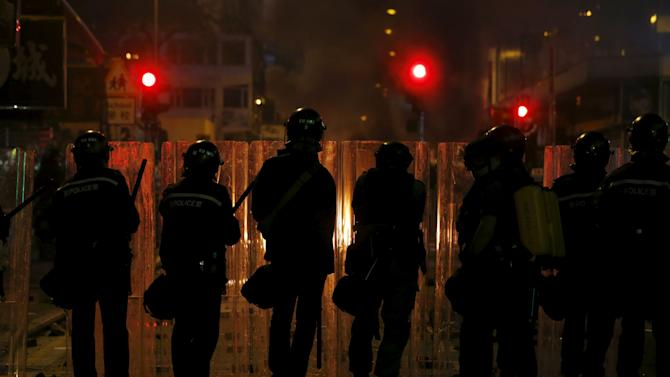 Riot police stand in front of a fire set by protesters at a junction at Mongkok shopping district in Hong Kong