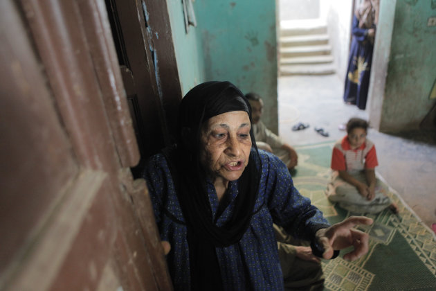 In this Thursday, Aug. 2, 2012 photograph, Egyptian Christian Sameeha Wehba, 70, the only Christian who remains at Dahshour village, is hosted by Muslim family of Mahmoud Abou Abdel Karim, at Dahshour