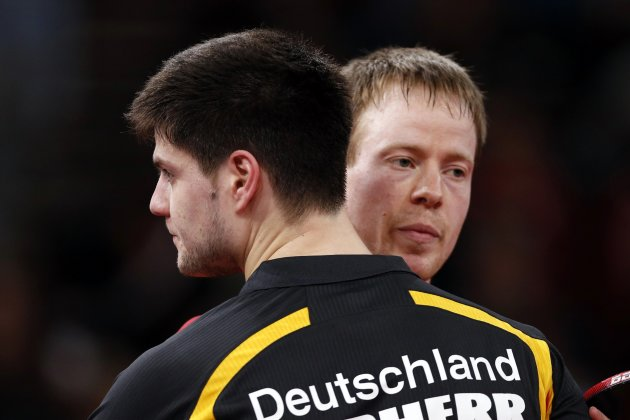 Baum of Germany passes his compatriot Ovtcharov after their men's singles fourth round match at the World Team Table Tennis Championships in Paris