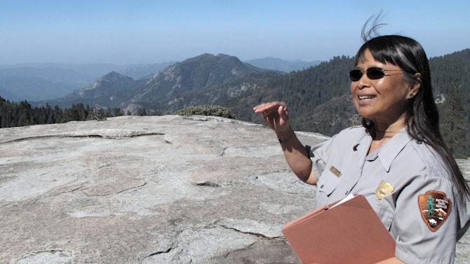 In this May 11, 2012 photo, Sequoia National Park air resource specialist Annie Esperanza explains how ozone diminishes the view from Beetle Rock in Sequoia National Park, Calif. A big city problem has settled in a big way in Sequoia Kings Canyon National Park, home of the giant Sequoias. Smog from the neighboring Central Valley is making it tougher for seedlings from the giants to take hold, and the needles of surrounding Jeffrey and Ponderosa pines are yellowing. (AP Photo/Tracie Cone)