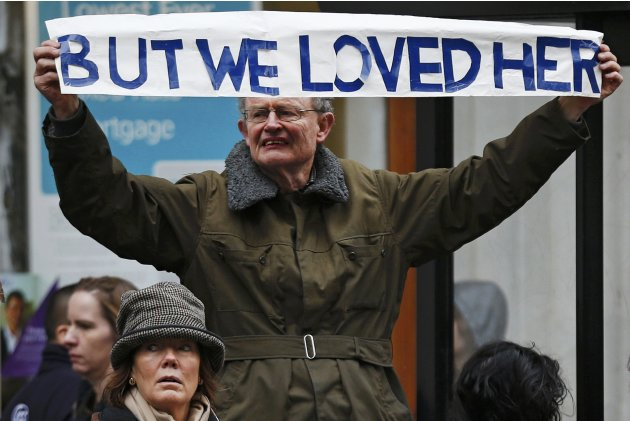 A man holds up a banner before former British PM Thatcher's funeral procession in London