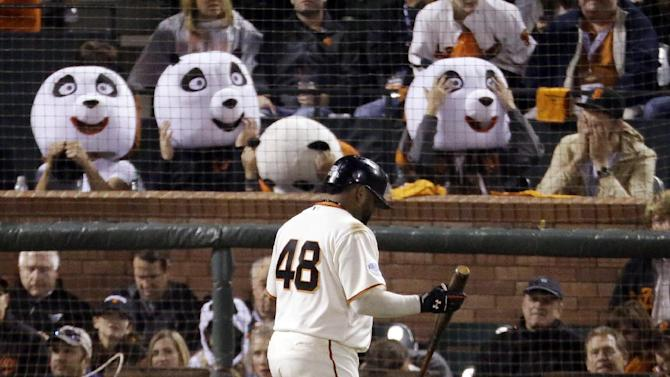 "FILE - This Oct. 25, 2014, file photo shows San Francisco Giants' Pablo Sandoval walking past fans wearing panda heads after he strikes out during the third inning of Game 4 of baseball's World Series against the Kansas City Royals in San Francisco. With Sandoval's departure to the Boston Red Sox this week, Giants fan Sam Li says he and his friends have decided they must find a new way to honor their home team than those heads honoring the third baseman's ""Kung Fu Panda"" nickname.(AP Photo/Charlie Riedel, File)"