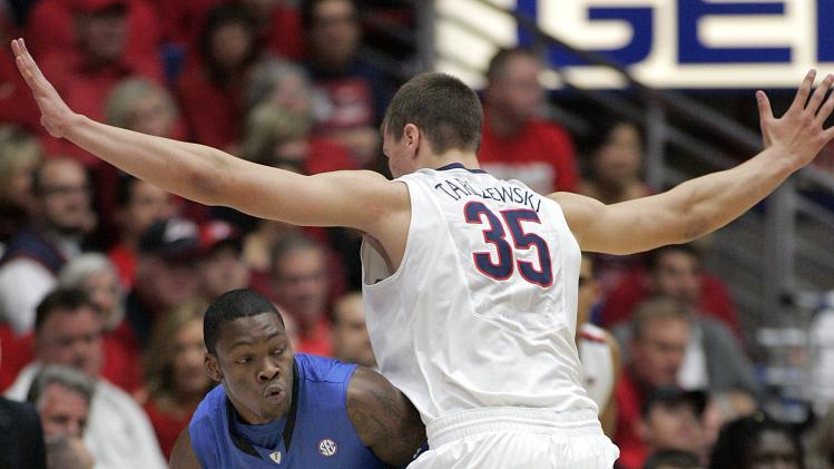 Florida's Michael Frazier II (20) attempts to dribble around the defense of Arizona's Kaleb Tarczewski (35) during the first half of an NCAA college basketball game  at McKale Center in Tucson, Ariz.,Saturday, Dec. 15, 2012. (AP Photo/John Miller)
