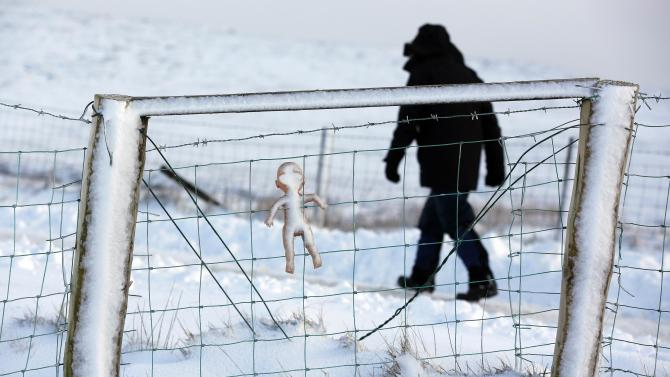A child's doll is placed on a fence near an illegal dump on Slieve na Orra mountain near the village of Cargan after heavy snow led to traffic disruptions and the closure of schools across Northern Ireland
