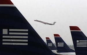 An American Eagle jet takes off as U.S. Airways jets are lined up at Reagan National Airport in Washington