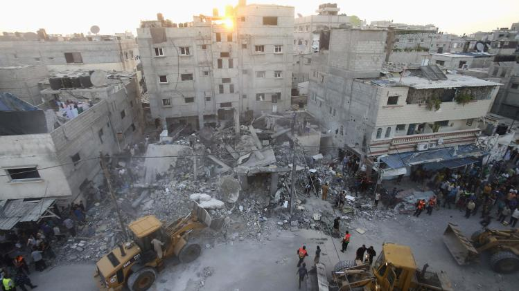 Palestinians and rescue workers search for victims under the rubble of a house which police said was destroyed in an Israeli air strike in Rafah