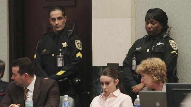 Casey Anthony, center, sits at the defense table, with her attorneys, Jose Baez, left, and Dorothy Clay Sims waiting for the jury to return with the verdict in her murder trial at the Orange County Courthouse in Orlando, Fla., Tuesday, July 5, 2011. The jury acquitted Anthony of mudering her daughter, Caylee.  (AP Photo/Red Huber, Pool)