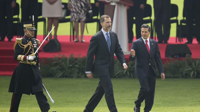 Spain's King Felipe VI, center, and Mexico's President Enrique Pena Nieto, walk out to review an honor guard during a welcoming ceremony at the Campo Marte military field in Mexico City, Monday, June 29, 2015. The Spanish royals are in Mexico for an official four-day visit. (AP Photo/Eduardo Verdugo)