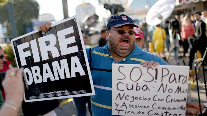 People stand outside the Little Havana restaurant Versailles, as they absorb the news that President Barack Obama wants to change the US Cuba policy on December 17, 2014 in Miami
