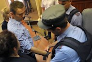 A police officer handcuffs Russian opposition leader Alexei Navalny (L) in the courtroom in Kirov, northern Russia on July 18, 2013. Navalny is pulling out of the Moscow mayoral race and is calling on his supporters to boycott the vote, his election chief said Thursday