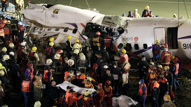 File photo of rescuers removing a body in a bag after a TransAsia Airways plane crash landed in a river in New Taipei City
