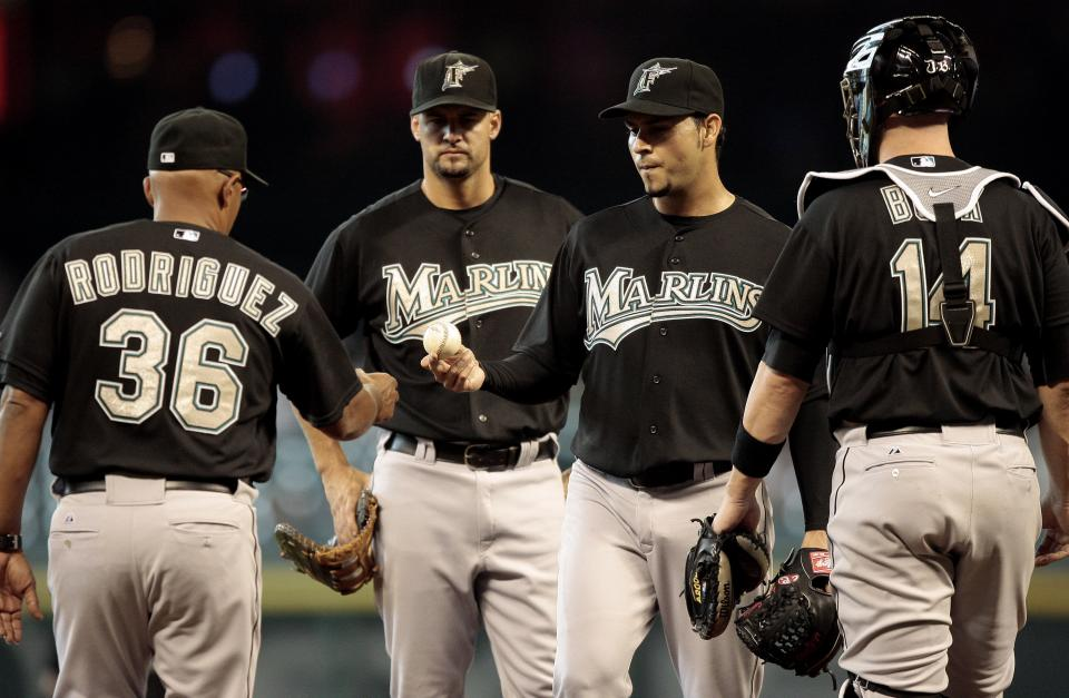 Florida Marlins' Anibal Sanchez,  second from right, hands the ball to manager Edwin Rodriguez (36) as catcher John Buck, right, looks on as Sanchez was removed from the baseball game in the fifth inning against the Houston Astros, Sunday, April 10, 2011, in Houston. (AP Photo/Bob Levey)