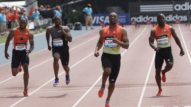 Tyson Gay, second from right, crosses the finish line ahead of the pack during the 100-meter B race at the Adidas Grand Prix track and field meet on Randall's Island, Saturday, June 9, 2012, in New York.  (AP Photo/Mary Altaffer)