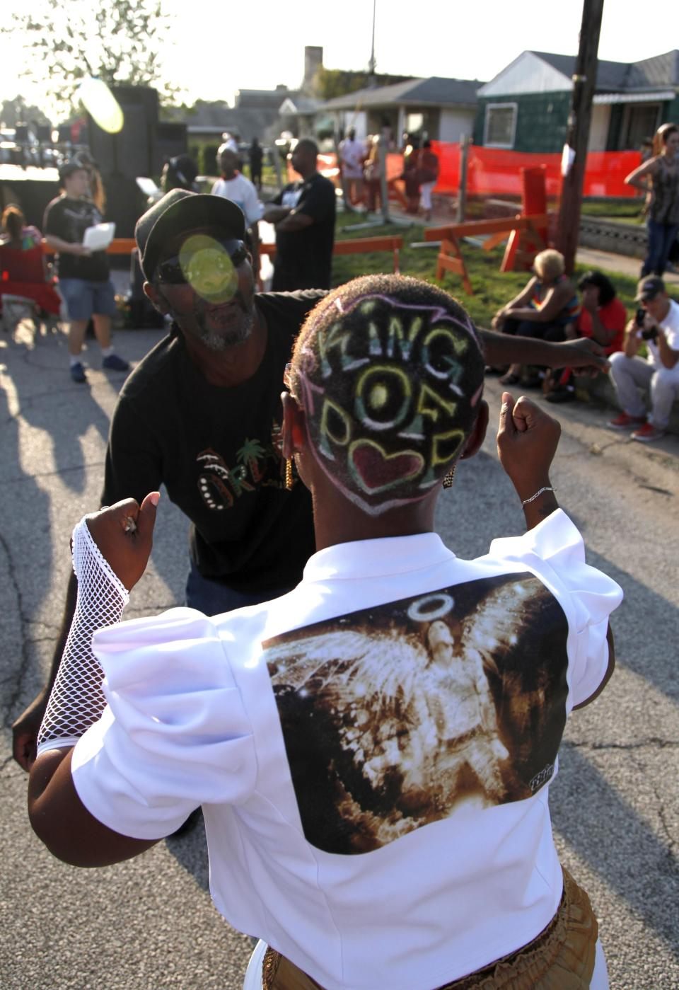Angela Burnham and Lawrence Quarles dance to recorded music outside Jackson's boyhood home during celebrations marking what would have been Jackson's 54th birthday Wednesday, Aug. 29, 2012, in Gary, Ind.  (AP Photo/Charles Rex Arbogast)