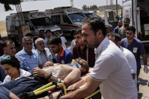 Medics carry a wounded man that arrived from the Syrian…