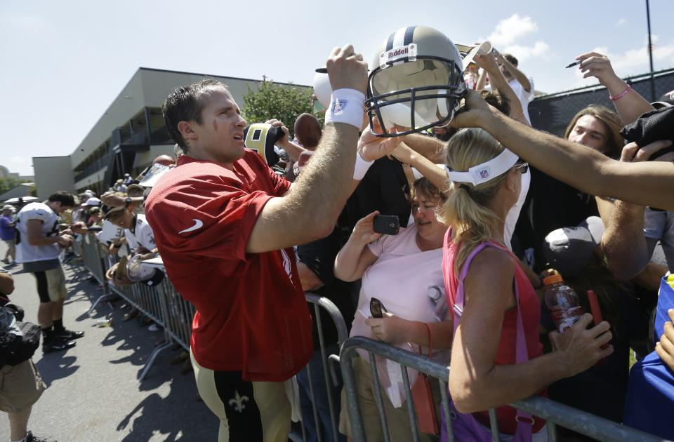 New Orleans Saints quarterback Drew Brees (9) signs autographs during their NFL football training camp in Metairie, La., Monday, July 29, 2013. (AP Photo/Gerald Herbert)