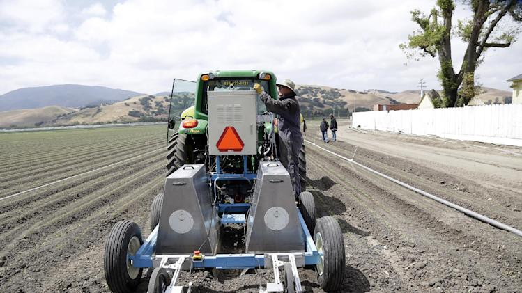 In this May 23, 2013, photo, field operations manager Matthew Rossow tests the lettuce bot in Salinas, Calif. In the Salinas Valley, the lettuce capital of the world, entrepreneurs with the Silicon Valley company Blue River Technology are testing the Lettuce Bot, a boxy robotic machine that can thin fields of lettuce, a job that now requires detailed hand work by 20 farm workers. (AP Photo/Marcio Jose Sanchez)