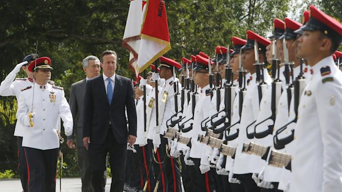 Britain's PM David Cameron inspects an honour guard with his Singaporean counterpart Lee Hsien Loong during a welcome ceremony at the Istana in Singapore