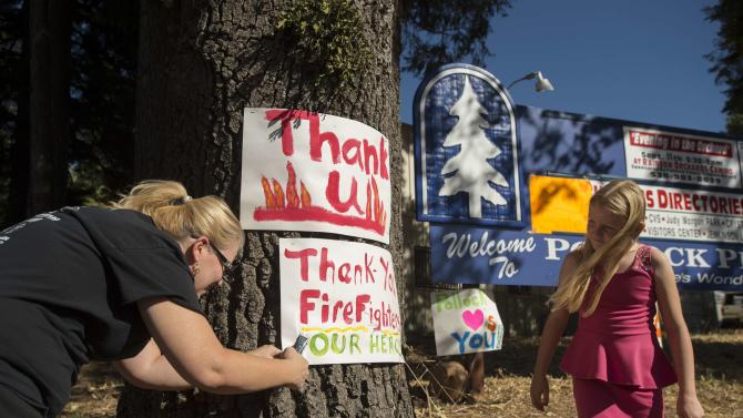 "A woman displays a ""thank you"" sign for firefighters battling the King Fire in Pollock Pines, California"