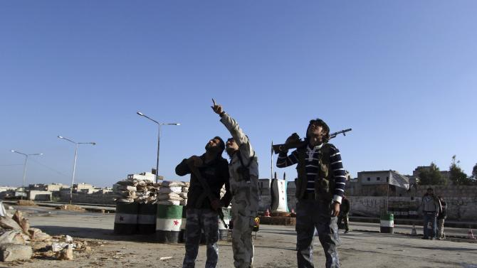 Rebel fighters of al-Jabha al-Shamiya look at the sky, at a checkpoint they are manning in Masaken Hanano neighbourhood of Aleppo