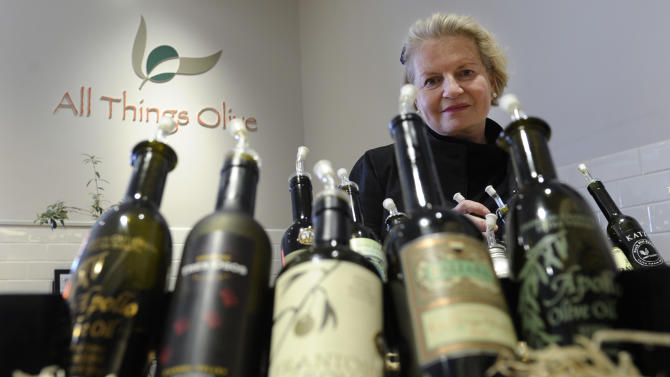 """This photo taken Feb. 12, 2014 shows California Olive Oil Council Executive Director Patricia Darragh posing with a collection of California olive oil at the All Things Olive shop in Washington. It's a pressing matter for the tiny U.S olive oil industry. Shoppers are more often pouring European oil _ it's cheaper and viewed as more authentic than the American competition. And that's pitting U.S. producers against importers of the European oil. Some liken the battle to the California wine industry's struggles to gain acceptance decades ago. The tiny California olive industry says European olive oil filling U.S. shelves often is mislabeled and lower grade. They're pushing the federal government to give more scrutiny to imported varieties. One congressman-farmer even goes as far as suggesting labels on imported oil say """"extra rancid"""" rather than extra virgin. Stricter standards might help American producers grab more market share from the dominant Europeans. (AP Photo/Susan Walsh)"""