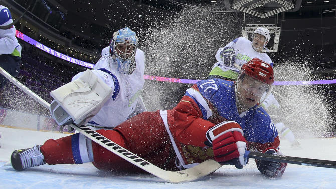 Slovenia goaltender Robert Kristan reaches over Russia forward Alexei Tereshenko as they fall to the ice at the goal in the first period of a men's ice hockey game at the 2014 Winter Olympics, Thursday, Feb. 13, 2014, in Sochi, Russia. Russia won 5-2. (AP Photo/Bruce Bennett, Pool)
