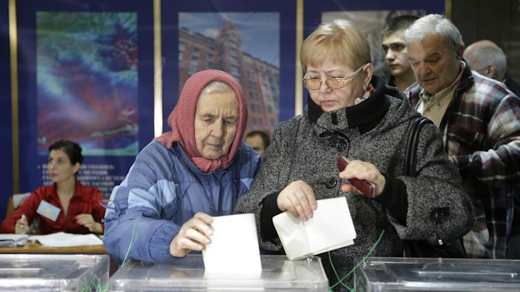 Ukrainians cast their ballots at a polling station in Kiev, Ukraine, Sunday, Oct. 28, 2012. Ukrainians are electing a parliament on Sunday in a crucial vote tainted by the jailing of top opposition leader Yulia Tymoshenko and fears of election fraud. (AP Photo/Efrem Lukatsky)