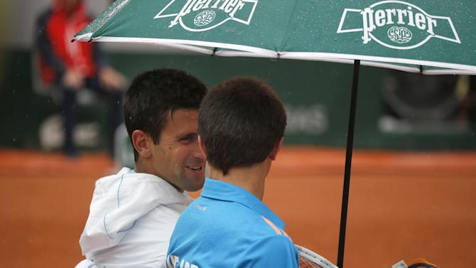 Serbia's Novak Djokovic, left, talks to a ball boy after inviting him to sit on his bench during a break during the first round match of the French Open tennis tournament against Portugal's Joao Sousa at the Roland Garros stadium, in Paris, France, Monday, May 26, 2014