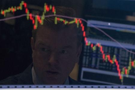 A specialist trader is reflected on his screen on the floor of the New York Stock Exchange
