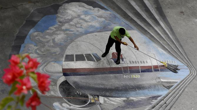 "FILE - In this April 8, 2014, file photo a school utility worker mops a mural depicting the missing Malaysia Airlines Flight 370 at the Benigno ""Ninoy"" Aquino High School campus at Makati city east of Manila, Philippines. After the shooting down of Malaysia Airlines Flight 17 on Thursday, July 17, 2014, Malaysia is now grappling with the horrific loss of two of its airplanes, just four months apart. (AP Photo/Bullit Marquez, File)"