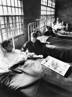 FILE - In this June 25, 1945 picture, army doctors expose patients to malaria-carrying mosquitoes in the malaria ward at Stateville Penitentiary in Crest Hill, Ill. Around the time of World War II, prisoners were enlisted to help the war effort by participating in studies that could help the troops. A series of malaria studies at Stateville Penitentiary in Illinois and two other penitentiaries were designed to test antimalarial drugs that could help soldiers fighting in the Pacific. Shocking as it may seem, government doctors once thought it was fine to experiment on disabled people and prison inmates. (AP Photo/File)