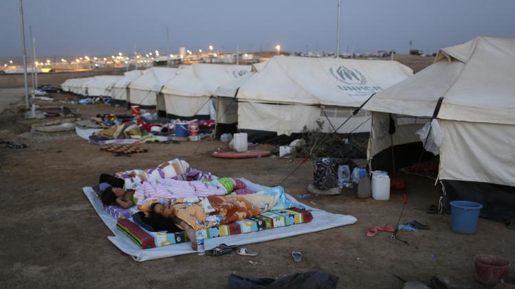 Displaced people from the minority Yazidi sect sleep on the ground at Bajed Kadal refugee camp, southwest of Dohuk province
