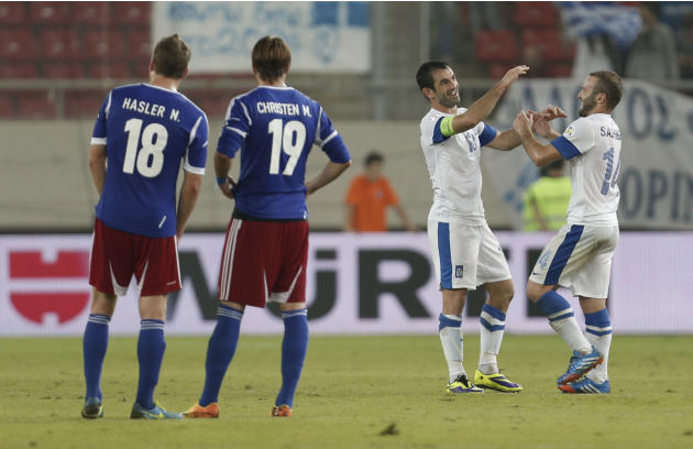 Greece's Giorgos Karagounis, second right, scorer of the second goal and Dimitris Salpingidis, right, scorer of the first goal, celebrate during their World Cup Group G qualifying soccer match against