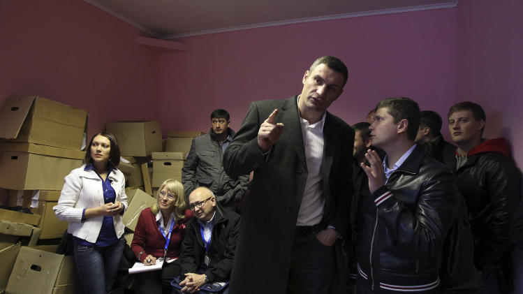 Chairman of the Ukrainian opposition party Udar (Punch) and WBC Heavyweight Champion boxer Vitali Klitschko, center, speaks with members of the election commission at their office in Brovary, Ukraine, Tuesday, Oct. 30, 2012. Ukrainian opposition parties are scrambling for position after the ruling party scored a confident victory in parliamentary elections denounced as unfair by international observers. (AP Photo/Olexander Kosarev)