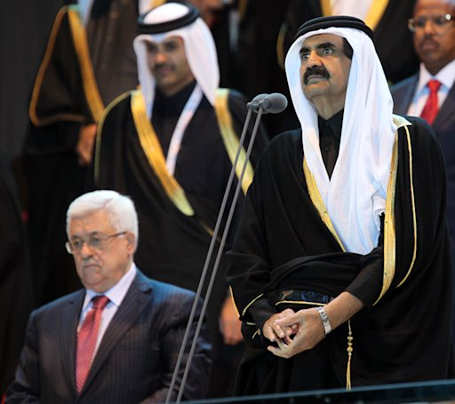 Palestinian President Mahmoud Abbas , left,  listens to the Emir of Qatar, Sheikh Hamad bin Khalifa , right, addressing the opening ceremony of the pan-Arab Games in Doha on Friday, Dec 9, 2011. More than 5,000 Arab athletes are participating in the Arab games from Dec 9, to 24. (AP Photo / Osama Faisal)