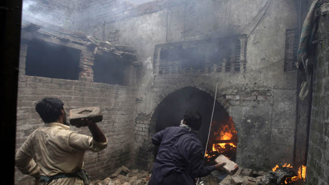 Pakistani men, part of an angry mob, throw bricks at a Christian house after setting it on fire, in Lahore, Pakistan, Saturday, March 9, 2013. A mob of hundreds of people in the eastern Pakistani city of Lahore attacked a Christian neighborhood Saturday and set fire to homes after hearing accusations that a Christian man had committed blasphemy against Islam's prophet, said a police officer. (AP Photo/K.M. Chaudary)