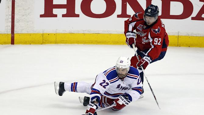 New York Rangers defenseman Dan Boyle (22) dives to pass the puck with Washington Capitals center Evgeny Kuznetsov (92), from Russia, behind, during the third period of Game 3 in the second round of the NHL Stanley Cup hockey playoffs Monday, May 4, 2015, in Washington. The Capitals won 1-0. (AP Photo/Alex Brandon)