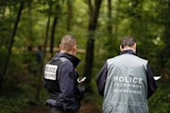 French policemen at the Bois de Vincennes in Paris on June 18 after a second human torso was discovered in the woods. Police said Monday they were holding for questioning a couple suspected of having killed and dismembered another couple and dumped their headless torsos in the forest on the edge of Paris