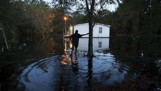 Lewis Johnson makes his way to help a neighbor remove valuables from a flooded home on Frank Williams Road in Georgetown