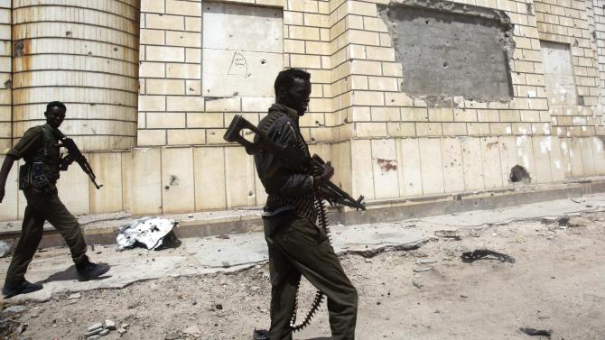 Somali government soldiers patrol near the scene of a suicide car explosion outside the Somali parliament building in Mogadishu