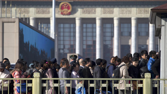 A Chinese paramilitary policeman, center back, stands guard as people line up for security check before entering Tiananmen Square in Beijing Thursday, Nov. 1, 2012. Beijing is tightening security as its all-important Communist Party congress approaches, and some of the measures seem bizarre. Most of the security measures were implemented in time for Thursday's opening of a meeting of the Central Committee. (AP Photo/Andy Wong)
