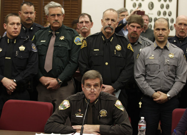 Weld County Sheriff John Cooke, center, backed by a group of fellow sheriffs, testifies against proposed gun control legislation in the Colorado Legislature, at the State Capitol, in Denver, Monday March 4, 2013. State Senate committees began work Monday on a package of gun-control measures that already have cleared the House which include limits on ammunition magazine sizes and expanded background checks to include private sales and online purchases. (AP Photo/Brennan Linsley)