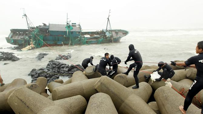 South Korean coast guard officers try to rescue Chinese fishermen from a Chinese ship that ran aground in Jeju, South Korea, Tuesday, Aug. 28, 2012. A powerful typhoon pounded South Korea with strong winds and heavy rain Tuesday, while the nation's coast guard battled rough seas in a race to rescue fishermen on two Chinese ships that slammed into rocks off the southern coast. (AP Photo/Newsis, Kang Jae-nam) KOREA OUT